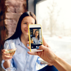 Happy friends celebrate holiday home Woman taking photo smartphone
