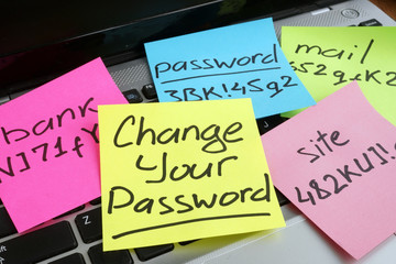Change your password. Laptop with pieces of paper.