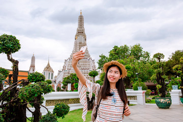 Beautiful Asian woman selfie with smartphone at wat Arun temple on vacation