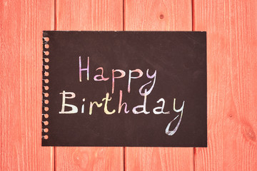 sheet of black paper from a notebook, with a colors inscription Happy birthday, lies in the center of the frame on a textured wooden surface living coral color, top view, flat lay