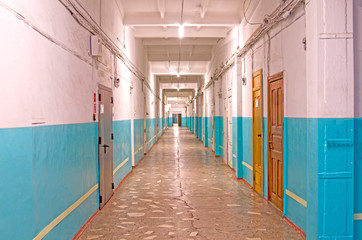 A long corridor with doors to offices. Marble floors, mirrored ceiling. Old industrial building.
