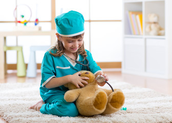 Kid weared doctor clothes playing with teddy bear in nursery