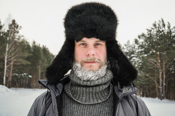 Siberian Russian man with a beard in hoarfrost in freezing cold in the winter freezes in a village in a snowdrift and wears a hat with a earflap.
