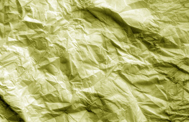 Crumpled sheet of paper in yellow color.