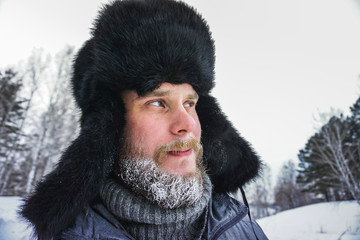 frozen man with a beard in winter in a forest with snowdrifts fell ill from the cold after a walk in the village