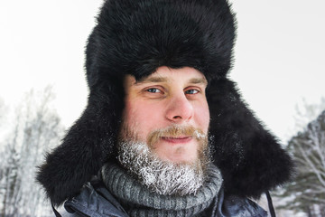 Happy Siberian Russian man with a beard smiles and lets out steam from his mouth in hoarfrost in freezing cold in the winter freezes in a village in a snowdrift and wears a hat with a earflap.