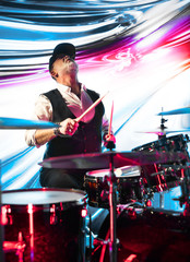 Professional drummer playing on drum set on stage in the color light