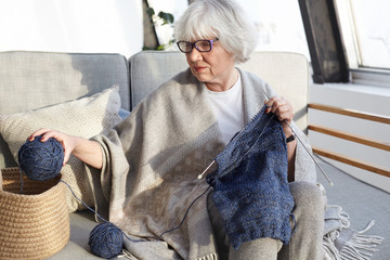 Attractive talented Caucasian grandmother in eyeglasses enjoying her hobby sitting comfortably on sofa, holding yarn ball and kneedles, knitting sweater for her husband. People, age and leisure