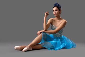 Slim ballerina in blue dress sitting on floor in studio