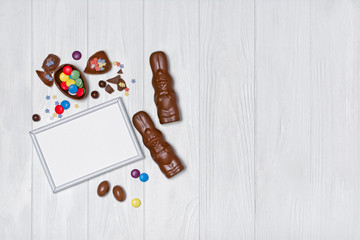 Mock up of blank white frame with traditional easter sweets as chocolate bunnies and eggs