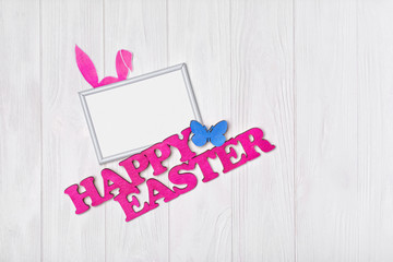 Mock up of blank white frame with pink text of happy easter and bunny ears