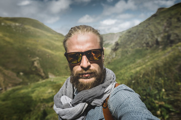 Global Travel Concept. Young Hiking Man In Sunglasses Take A Selfie On A Background Of A Mountain Landscape