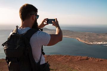 Silhouette of a man on the background of the Atlantic Ocean and the island of La Graciosa. Mountain. Mirador del Rio. North of Lanzarote. Canary Islands. Spain