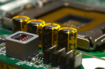 close up of components with capacitors on electronic pc motherboard