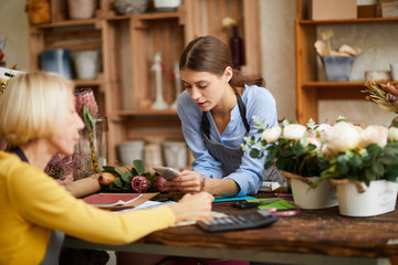 Portrait of two female business owners managing flower shop, copy space