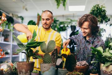 Two man watering plants in flower shop.