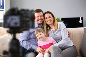 Happy adult millenial family photographed while sitting at home on the couch camera is on a tripod timer. Wife writes articles on family life in her blog publicist ideal family values concept.