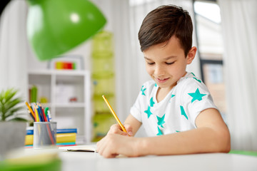 education, childhood and school concept - happy little boy sitting at desk and writing or drawing to notebook by pencil at home