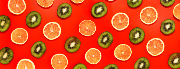 Wall Mural - Lemon and kiwifruit slices in lines with hard shadows on red background, flat lay image.