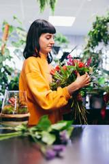 Woman composing flower bouquet in flower shop.