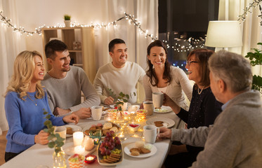 celebration, holidays and people concept - happy family having tea party at home