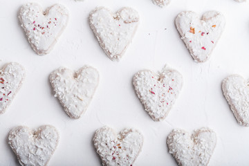 A pattern of Valentine's day white coconut heart shaped cookies on a white background  with red sprinkles. Copy space. Monochrome