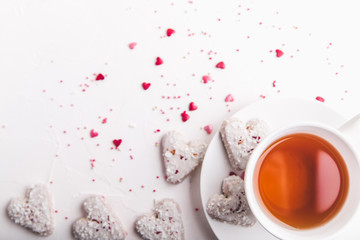 White tea cup with tea and Valentine's day white coconut heart shaped cookies with red and pink heart sprinkles. Copy space