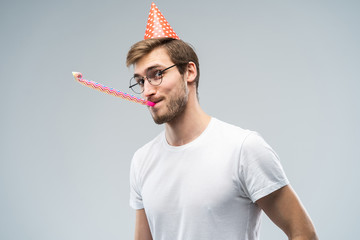Studio shot of unshaven young Caucasian male blowing whistle while celebrating birthday, having relaxed and cheerful expression on his face