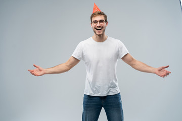 People, joy, birthday, anniversary, fun and party concept. Picture of handsome astonished young man with cone hat on his head celebrating birthday among friends, amazed with unexpected gift.