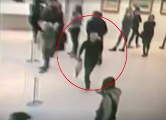A screen grab taken from video footage shows a man walking with a painting by prominent artist Arkhip Kuindzhi at Tretyakov art gallery in Moscow