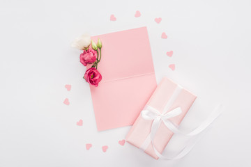 top view of empty card, paper hearts and gift box isolated on white