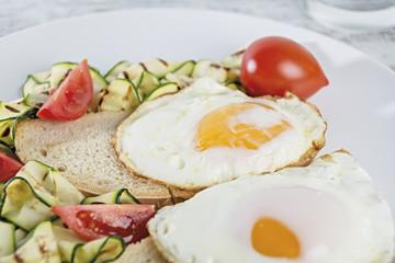 uovo fritto sopra fetta di pane e zucchine grigliate sopra tavola rustica