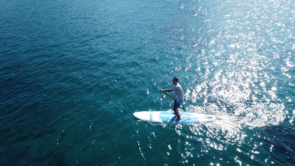 Aerial drone top view photo of young fit man exercising Stand Up Paddle surf board or sup in mediterranean turquoise sea sandy beach
