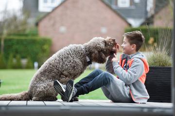 Junge gibt Hund ein Leckerli