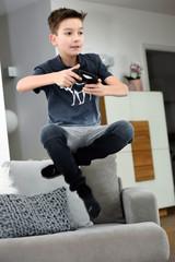 Junge springt beim Konsolen spielen in die Luft