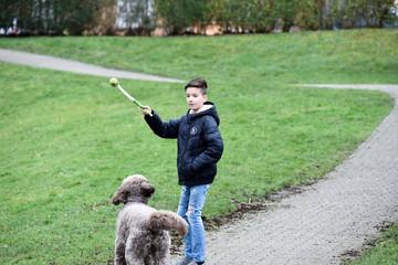 Junge spielt Ball mit seinem Hund