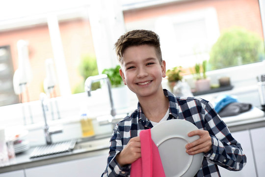 Junge trocknet Teller ab