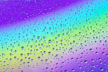 Drops on the glass against the background of the rainbow, texture and background