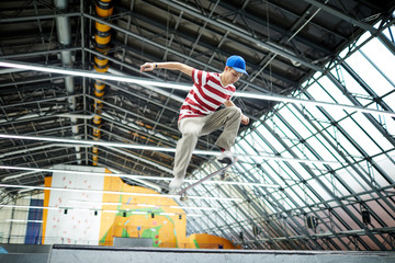 Young casual freestyler jumping on skateboard over edge of descent during training at stadium