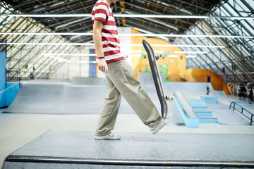 Teenage parkour boy holding skateboard on his foot while exercising on skateboarding area