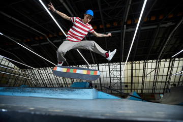 Skilled guy in casualwear jumping over skateboarding area and flying above his skateboard
