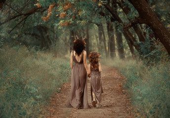 creative family photo of brunette mother and blond daughter, fauns hold hands and go deep into the forest along an abandoned secret path, dressed in long light brown dresses with cutouts on the back