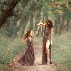 fairy mother deer on path spinning her daughter on a forest trail, wearing long brown dresses, showing her charming leg in a cut, fabulous fauns are having fun and dancing, creative shooting