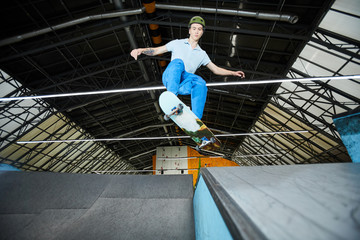 Active skilled guy in casualwear and helmet standing on skateboard in jump over edge and descent during training