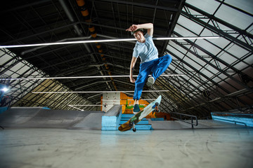 Active boy jumping in air over his skateboard while practicing parkour stunts during workout