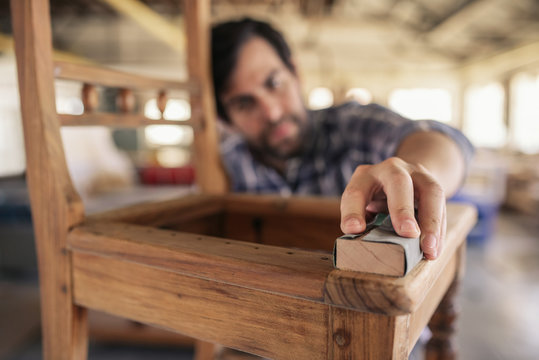 Skilled woodworker sanding a chair in his workshop