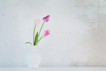 tulips in white vase on background old wall
