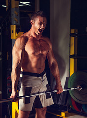 Energetic strong man lifting barbell in crossfit gym and loud agressive shouting on dark sport club background. Low section of dedicated.