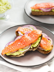 Avocado toast with salmon slice and onion on gray background - vertical closeup photo.