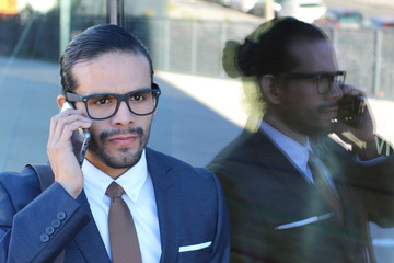 Angry businessman with his reflection calling by phone